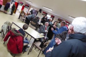 Photograph of public meeting in Quarrington Hill community centre. there is a man with grey hair in the foreground and a boy sitting at a table.