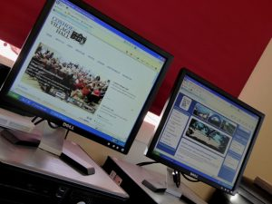 Photograph of two computer screens showing local websites