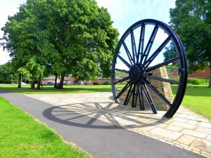 Photograph of the Pit Wheel on the village green with shadow about 2014 taken in bright conditions.Trees are in the background