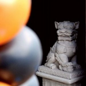 Photograph of a stone Chinese dragon with a black and orange ball in front
