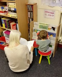 Photograph of grandparent reading with child