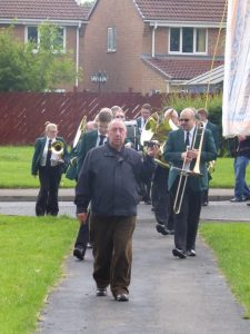 Photograph of bannner group chair leading march