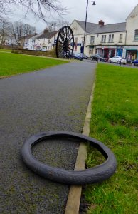 Photograph of tyre dumped on village green