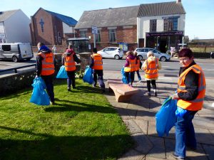Photograph of volunteer litter pickers in action outside village hall