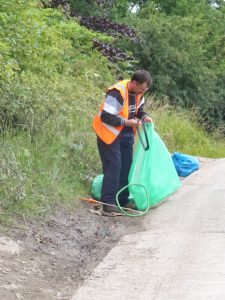 Photograph of volunteer litter picker at work with green litter collection bags
