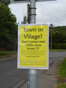 Photograph of sign publicising impact of 1000 houses in Coxhoe during survey. with headline Does Coxhoe need 1000 more houses