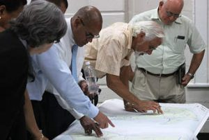 Photo of people looking at plans. one man is pointing at something on them and one has hands on hips