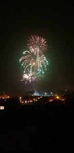Image of fireworks going off trailing lights