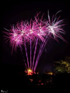 Image of fireworks going off purple and white