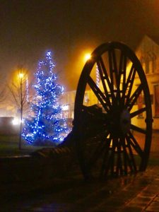 Photograph of Christmas Tree on Village Green with Christmas Lights and Pit Wheel