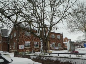 Photograph of village hall with snow and wierd brick pattern effect. Very snowy scene.