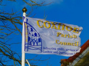 Photograph of the flag of Coxhoe Parish council flying in wind, with bright blue sky