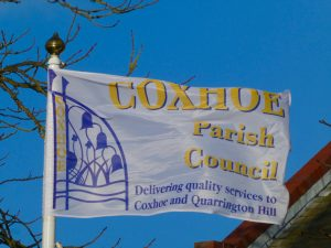 Parish Council flag flying in sun with the word Coxhoe unfolded and bright blue sky in the background
