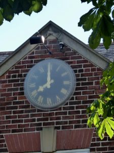 Photograph of millennium clock on village hall with leaves in foreground