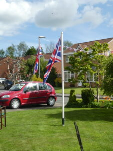 Photograph of two flags on masts in a garden