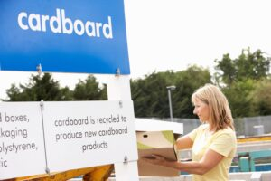 Photograph at a household waste recycling centre with woman recycling carboard boxes