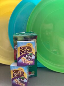 photo of frisbees, juice cartons and boxes of raisins