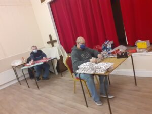 Volunteers wrapping Christmas parcels socially distanced